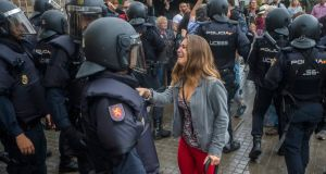 A woman addresses an officer of National Police outside a polling centre at Can Vilumara Secondary School in L'Hospitalet Llobregat, Barcelona. Photograph:  Quique Garcia/EPA