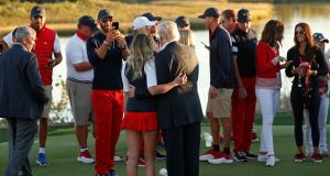 Dustin Johnson takes a photo of US President Donald Trump with his wife. Photograph: Reuters