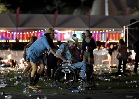 A man in a wheelchair is taken away from the Route 91 Harvest country music festival after a gunman opened fire on Sunday night.  Photograph: David Becker/Getty Images
