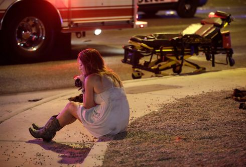 A woman sits on a curb at the scene following the shooting. Photograph: AP Photo/John Locher