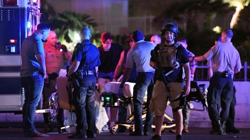 Police officers stand by as medical personnel tend to a person on Tropicana Ave near Las Vegas Boulevard. Photograph: Ethan Miller/Getty Images