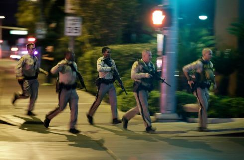 Police run to cover at the scene of a shooting near the Mandalay Bay resort and casino. Photograph: John Locher/AP