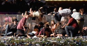 People scramble for shelter at the Route 91 Harvest country music festival after a shooting in Las Vegas, Nevada. Photograph:  David Becker/Getty Images