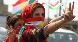 An Iraqi Kurdish woman wearing the Kurdish flag on her face flashes the victory gesture amid celebrations in the city of Kirkuk in northern Iraq last week. Photograph: Ahmad Al-Rubaye/AFP/Getty Images