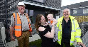 Helen Cheevers with her baby Erik outside their home in Ballymun, with Hugh Brennan of Ó Cualann cohousing alliance and architect Joe Kennedy. Photograph: Cyril Byrne