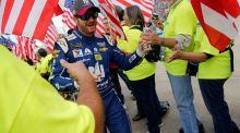 Dale Earnhardt Jr runs a gauntlet of fans with US flags as he is introduced before the start of the Monster Energy NASCAR Cup Series Apache Warrior 400 race in Dover. Photograph: Reuters
