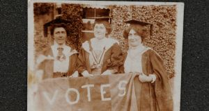 Suffragette and Irish nationalist Hanna Sheehy Skeffington, Kathleen Shannon and Kate Sheedy, in their graduation robes and mortar-boards, carrying a banner saying 'Votes' (for women)