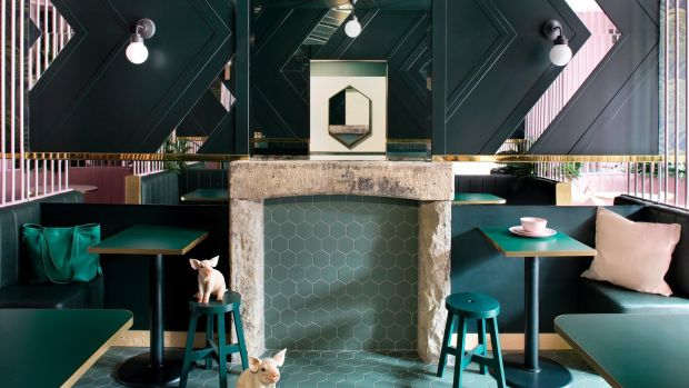 The pastel booths propped up by a backdrop of leaf-adorned wallpaper leading the eye to the hexagon teal tiles on the floor