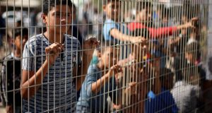 Palestinian boys stand by a fence as they wait for the arrival of Palestinian Prime Minister Rami Hamdallah and his government at Erez crossing in the northern Gaza Strip on Tuesday. Photograph: Mohammed Salem/Reuters
