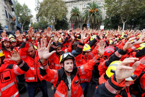 HANDS UP: Firefighters hold up their hands during a demonstration in Barcelona, Spain, against police actions during the banned Catalan independence referendum at the weekend. Photograph: Yves Herman/Reuters