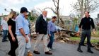 Donald Trump walks past hurricane wreckage as he participates in a walking tour  in Guaynabo, Puerto Rico on Wednesday. Photograph:  Jonathan Ernst/Reuters