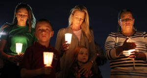 People in Las Vegas pray during a candlelight vigil for the shooting  victims. Photograph: Lucy Nicholson/Rueters