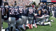 New England Patriots players hold hands and kneel during the national anthem prior to their match against the Houston Texans. Photograph: PA