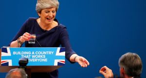 Philip Hammond hands a cough sweet to  Theresa May after she suffered a coughing fit whilst addressing the Conservative Party conference in Manchester. Photograph: Phil Noble/Reuters