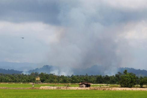 A helicopter flies near smoke on the Myanmar side as seen from Palang Khali, across the border in Bangladesh, October 3rd. Photograph: Damir Sagolj / Reuters