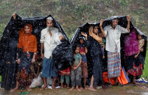Rohingya refugees shelter from the rain in a camp in Cox's Bazar, Bangladesh. Photograph: Cathal McNaughton  / Reuters