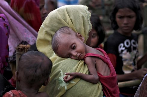 A woman carries an ill Rohingya refugee child through a camp in Cox's Bazar. Photograph: Cathal McNaughton / Reuters