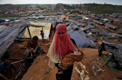 A Rohingya refugee carries her child in a refugee camp in Cox's Bazar. Photograph: Cathal McNaughton /Reuters