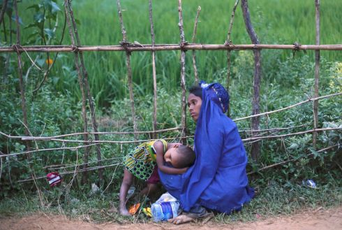 An exhausted Rohingya refugee woman rests with her daughter after jostling for aid outside a camp in Cox's Bazar.  Photograph: Danish Siddiqui /Reuters