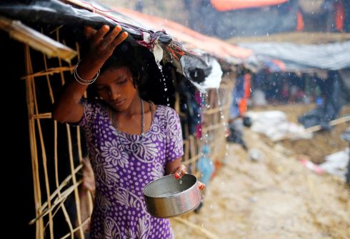 A Rohingya refugee girl collects rain water at a makeshift camp in Cox's Bazar.  Photograph: Mohammad Ponir Hossain /Reuters