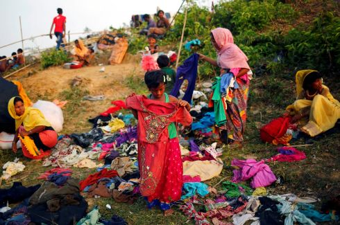 A Rohingya refugee girl checks clothes, which are donated by local people, in Cox's Bazar. Photograph: Mohammad Ponir Hossain  /Reuters