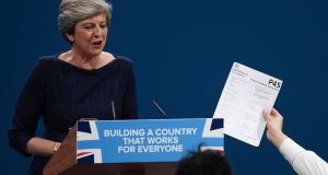 Comedian Simon Brodkin, aka Lee Nelson, hands prime minister Theresa May a P45 during her keynote speech to delegates and party members on the last day of the Conservative Party conference at Manchester Central. Photograph: Carl Court/Getty Images