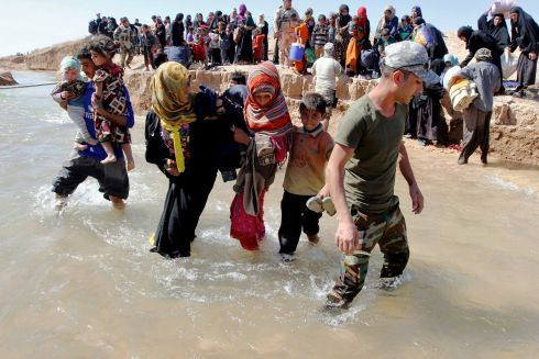 PICKING UP THE PIECES: Displaced people, who fled from their homes in Hawija, cross the water to reach the other bank to be transported to camps, southwest of Kirkuk, Iraq. Photograph: Ako Rasheed/Reuters