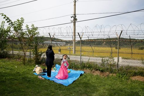 CHUSEOK: A South Korean mother and her daughter have an ancestor-memorial service as part of the Chuseok celebration near the border with the North near the demilitarized zone in Paju, South Korea. Photograph: Jeon Heon-Kyun/EPA
