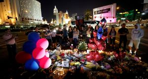People gather at a makeshift memorial in the middle of Las Vegas Boulevard on Wednesday. Photograph: Chris Wattie/Reuters