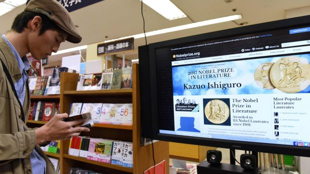 A man reads a book written by Japanese-born British novelist Kazuo Ishiguro at a book store in Tokyo today, after he won the Nobel Prize in Literature. Photograph: Kazuhiro Nogikazuhiro NOgi/AFP/Getty Images