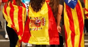 Youths wrapped in a Catalan, a Spanish and a Catalan separatist flag walk through a street  in Barcelona, Spain. Photograph: Jon Nazca/Reuters