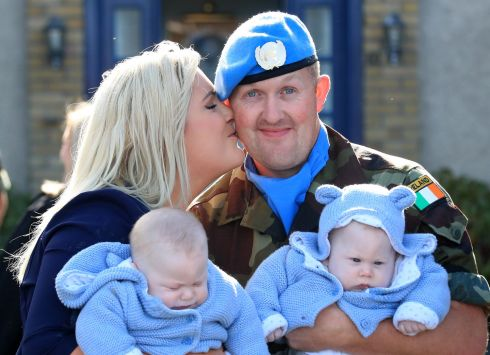 TWIN WELCOME: Pte Joe Foyle, of Laois, is welcomed home by his partner Deirdre Regan and their four-month-old twins Joe and Conor, at Casement Aerodrome when 100 Irish troops from the 55th Infantry Group, United Nations Disengagement Observer Force (UNDOF) returned home after a six-month deployment to the Golan Heights. Photograph: Colin Keegan/Collins