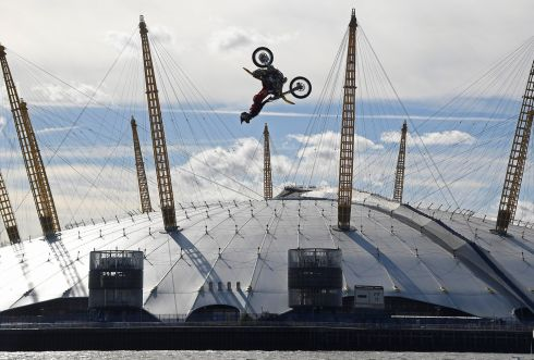 BARGE JUMP: Action sports performer Travis Pastrana somersaults on his motorbike as he jumps between two barges on the River Thames in London. Photograph: Toby Melville/Reuters