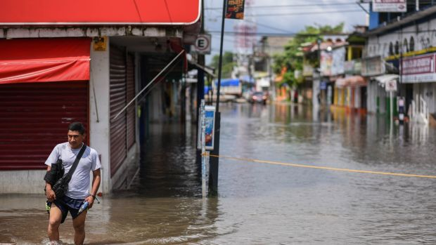 A man crosses a flooded street in the municipality of Minatitlan, south of the state of Veracruz, Mexico. Photograph: Angel Hernandez/EPA