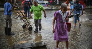 People walk through flooded streets in the municipality of Minatitlan, south of the state of Veracruz, Mexico, on Thursday. Photograph: Angel Hernandez/EPA