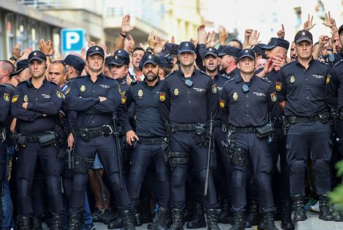 CATALONIA: Spanish National Police officers stand outside their hotel as they face locals protesting their presence in Pineda de Mar, north of Barcelona. Photograph: Albert Gea/Reuters
