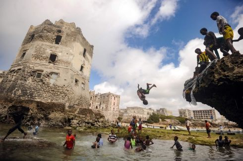 GERONIMO!: Somali children dive, play and swim in front of the ruins of an old building on the seashore of Hamarweyne district in Mogadishu. Photograph: Muhammad Abdiwahab/AFP/Getty Images