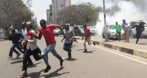 Supporters of the opposition coalition The National Super Alliance (NASA) and its presidential candidate Raila Odinga flee as the police fire tear gas  in downtown Nairobi, Kenya. Photograph: EPA/Daniel Irungu