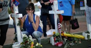 A woman cries at a makeshift memorial for victims of a mass shooting. Photograph: John Locher/AP