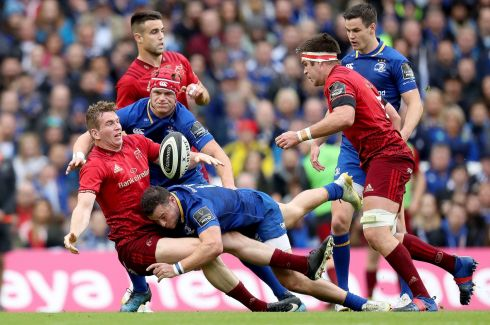 Munster's Chris Farrell offloads in tackle of Josh van der Flier and Robbie Henshaw of Leinster. Photograph: Billy Stickland/Inpho