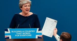 Protester comedian Simon Brodkin (R) gives a piece of paper written as a mock P45 (employee leaving form) to Britain's prime minister Theresa May (L) as she was delivering her speech on the final day of the Conservative Party annual conference on October 4th. Photograph: Paul Ellis/AFP/Getty Images