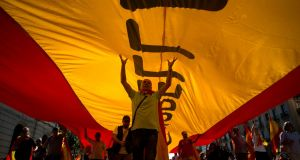 "Protesters hold a giant Spanish flag during a demonstration called by ""Societat Civil Catalana"" (Catalan Civil Society) to support the unity of Spain on October 8, 2017 in Barcelona. JORGE GUERRERO/AFP/Getty Images"
