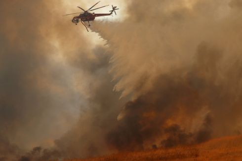 A helicopter drops water on a wind driven wildfire in Orange, California. Photograph: Mike Blake/Reuters