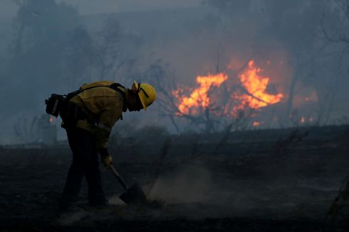 A firefighter works to put out hot spots on a fast moving wind driven wildfire in Orange, California. Photograph: Mike Blake/Reuters