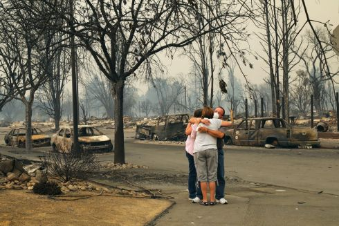 Tina and Art Anaya hug Lisa Coats on a street in the Coffey Park subdivision, where they all lost their homes to a wildfire in Santa Rosa, California. Photograph: Jim Wilson/The New York Times