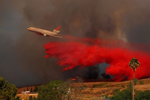 A DC-10 aircraft drops fire retardant on a wind driven wildfire in Orange, California. Photograph: Mike Blake/Reuters