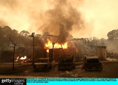 Burned out cars sit next to a building on fire in Santa Rosa, California. Photograph: Justin Sullivan/Getty Images
