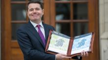 Raining maps and cogs: Minister for Finance Paschal Donohoe shows off Budget 2018. Photograph: Gareth Chaney/Collins
