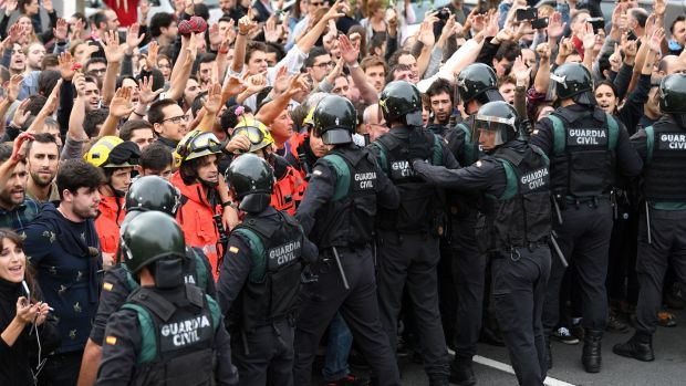 Catalan firefighters protect the crowds who raise their arms up as police move in during protests on the day of the unofficial independence referendum in Girona. Photograph: David Ramos/Getty Images