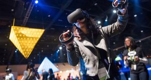 An attendee operates the Oculus VR Rift virtual reality  headset during the company's Connect 4 product launch event in San Jose, California